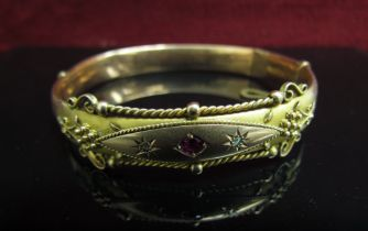 A Victorian 9ct gold bangle with scroll detail set with small old cut diamonds and ruby (dented),