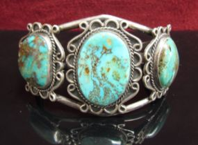A white metal bangle set with three oval turquoise in scroll mount