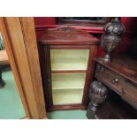 A late Victorian walnut cabinet with carved raised back over a glazed single door with key and