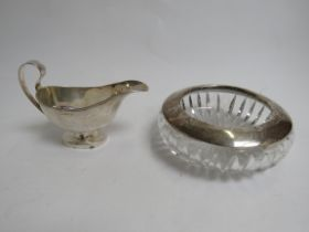A Samuel Levi silver sauce boat (a/f) and a silver rimmed presentation ashtray, marks rubbed,