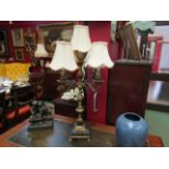 An ornate brass five sconce table electrolier with black and white square marble base on brass paw