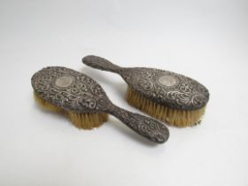 A pair of Victorian silver backed dressing table brushes, deep scrolled relief,