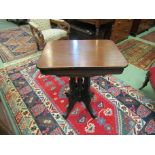 A Victorian round cornered top lamp table on a carved base and outswept legs,