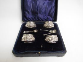 A Joseph Gloster Ltd silver set of four table salts with embossed floral design with spoons, cased,