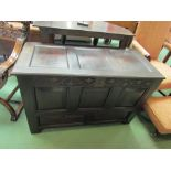 An 18th Century carved oak coffer with two faux drawers, the split hinge top over stile feet,