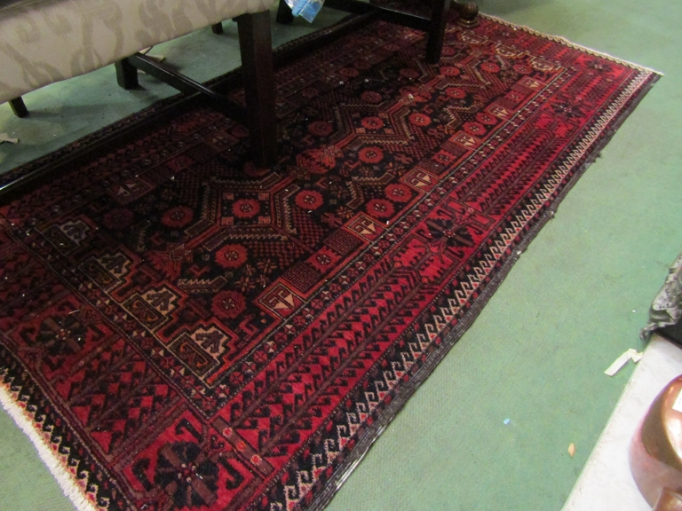 An Eastern black and red ground wool rug, central geometric field with multiple borders,