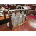 An early 20th Century three bottle Tantalus with two silver plated labels, decanters a/f.