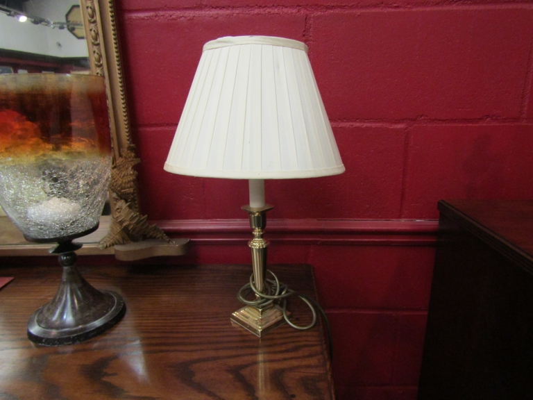 A pair of brass table lamps with cream pleated shades,