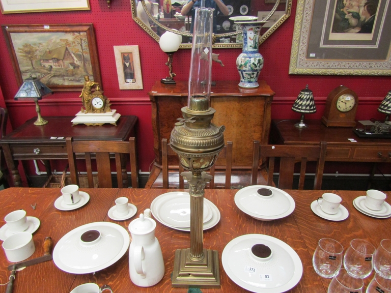 A brass oil lamp with acanthus Corinthian column, square stepped base,