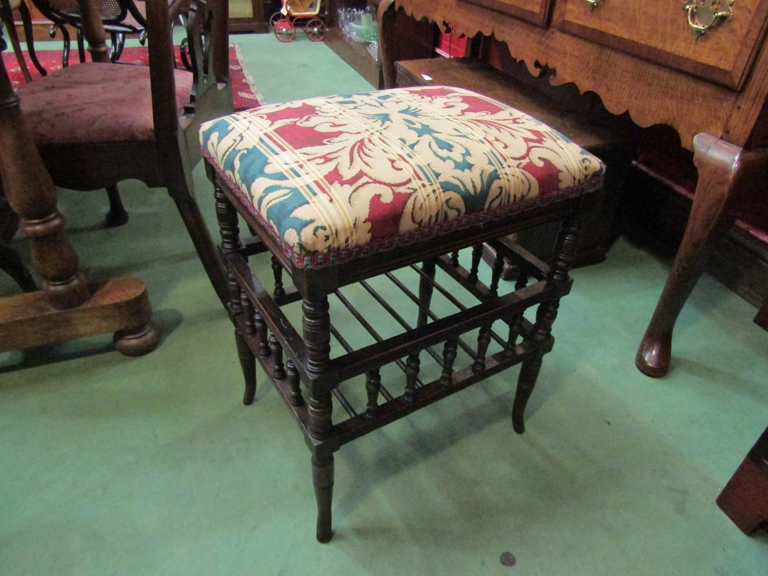 A late Victorian walnut piano stool on ring turned and spindle base with outswept feet