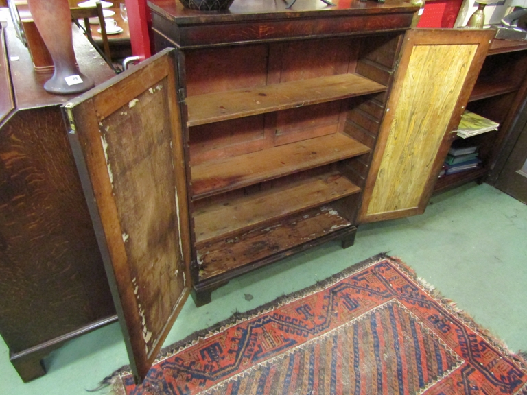 A George III oak bookcase, twin doors opening to reveal book space, on bracket feet. - Image 2 of 2
