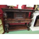 A 17th Century style carved oak press cupboard with single door over two drawers and pot board on