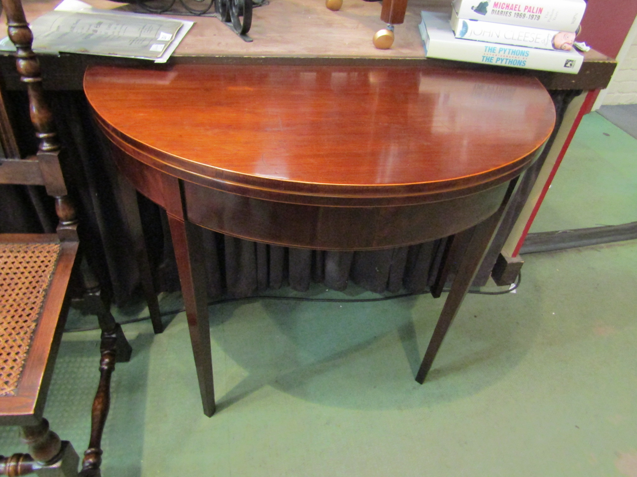 A George III mahogany bow front card table with satinwood line and ebony inlay on square tapering