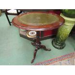 A Victorian walnut oval top wine table with gilt tooled leather inset on a turned column and tripod