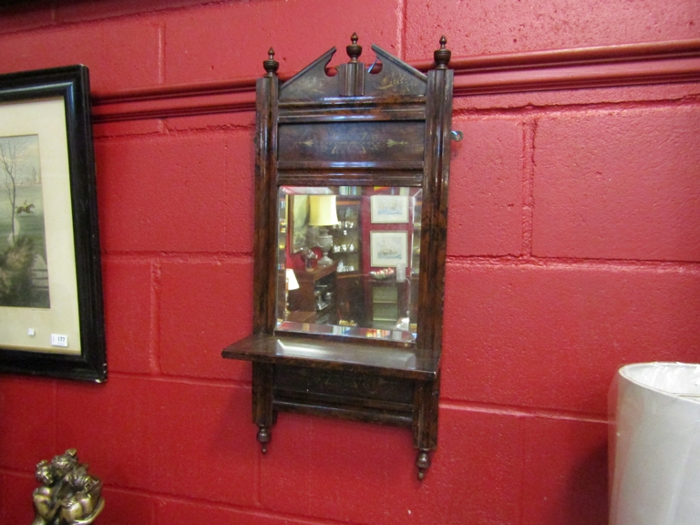 A lacquered rosewood effect wall mirror with shelf, 72cm x 32.