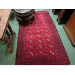 An Eastern red ground wool rug, central field of three rows of guls, multiple geometric borders,