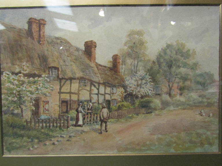 A watercolour depicting a row of thatched cottages, with people conversing, unsigned,