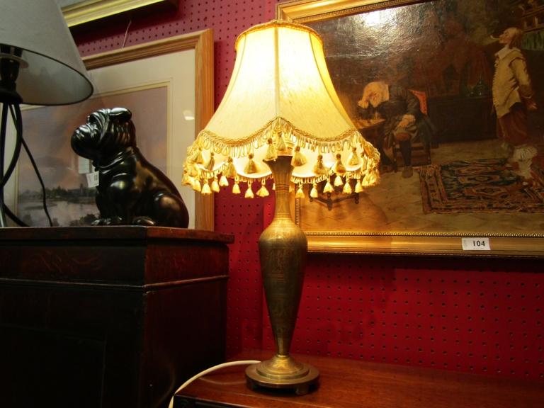 A brass table lamp with eastern pattern and shade.