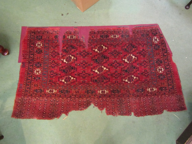 A 19th Century Eastern wool rug remnant, red ground, three rows of guls, blue border.