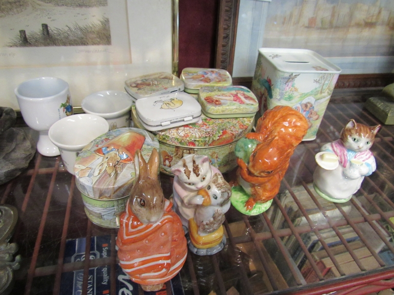 A quantity of Beatrix Potter items including four Beswick figures, tins and egg cups etc.
