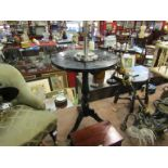 A Victorian lacquered circular tilt-top wine table on turned baluster column and tripod base with