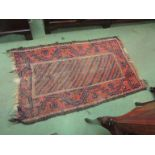 A late 19th Century Eastern wool rug, brown ground with terracotta and blue geometric pattern.
