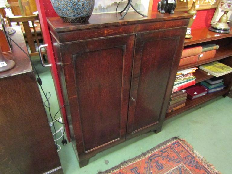 A George III oak bookcase, twin doors opening to reveal book space, on bracket feet.