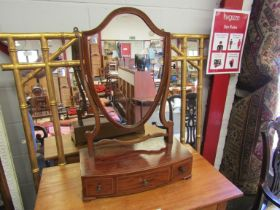 A Victorian flame mahogany shield back table-top mirror on three drawer base,