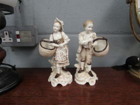 A pair of German porcelain figures holding baskets. Late 19th Century. 18.