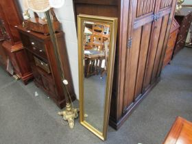 A slim gilt wall mirror,
