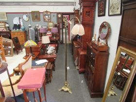 A Victorian brass standard lamp with crooked and scrolled arm joining a shade,