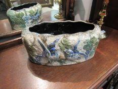 A glazed terracotta planter with blue bird design,