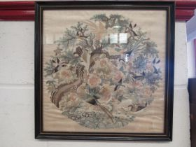 An embroidered silk depicting exotic birds, framed and glazed,