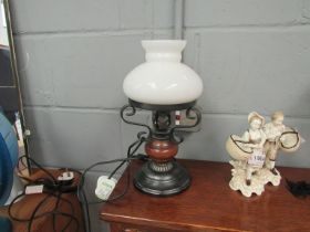 A table lamp as an oil lamp with white glass shade