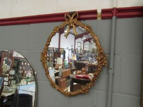 A gilt framed oval mirror with ribbon and swag frame,