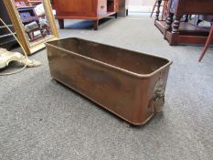 A copper planter with paw feet and lion head handles