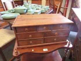 A yew wood seven drawer table top cabinet