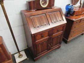 An old charm style oak bureau with linen fold detail,