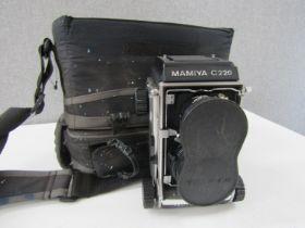 A cased Mamiya C220 medium format camera,