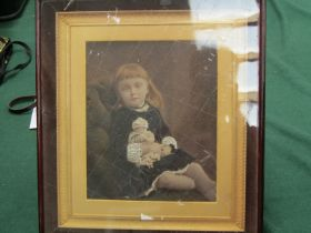 A 19th Century photograph portrait of seated girl with doll, highlighted,