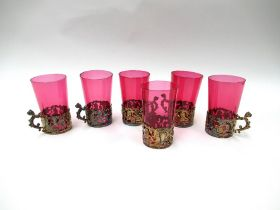 A set of six cranberry glasses with pierced cherubic holders
