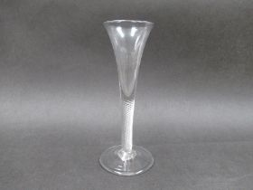 An 18th Century cloudy clear glass wine flute with air twist stem and domed foot with pontil mark.