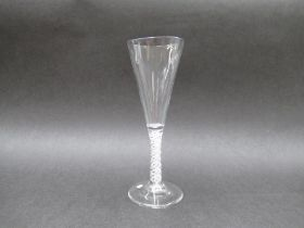 A mid 18th Century ale glass with funnel shaped bowl raised upon a double series opaque twist stem