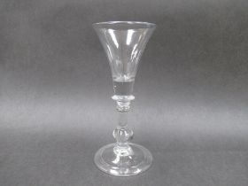 An early 18th Century wine glass with trumpet shaped bowl, solid at the base,
