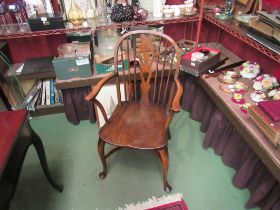 An elm and oak Windsor armchair the dished seat on cabriole legs and crinoline stretcher
