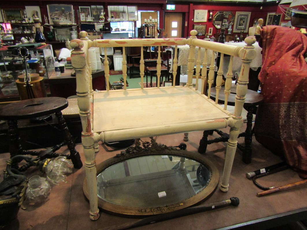 An Oriental style distressed painted dog/cat bed with spindle supports, knob finials on turned legs.