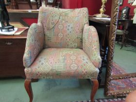 A mid 20th Century tub chair on sabre legs and enclosed arms with contemporary upholstery