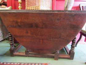 An 18th Century oak drop-flap table on bobbin turned legs and four stretchers