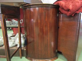 A George III style mahogany bow front wall hanging single door corner cupboard of small proportions