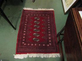A Pakistani Bokhara red ground rug with multiple borders,